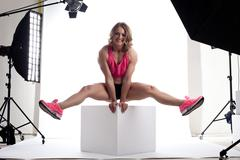 Beauty woman body builder sit on cube in studio Stock Photos