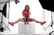 Stock Photo of beauty woman body builder sit on cube in studio