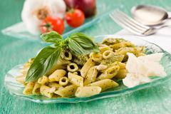 Pasta with pesto on green glass table Stock Photos