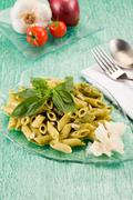 Stock Photo of pasta with pesto on green glass table
