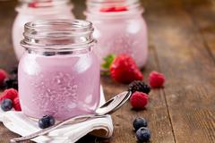 Small jars with homemade yogurt with berries Stock Photos