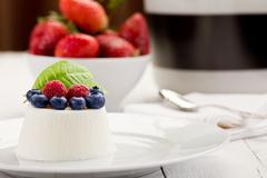 panna cotta with berries on white table - stock photo