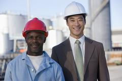 Multi-ethnic businessman and construction worker wearing hardhats Stock Photos