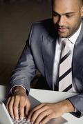 Stock Photo of African businessman typing on laptop