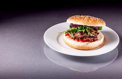 hamburger with arugula on grey surface - stock photo