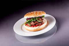 hamburger with arugula on grey surface - stock photo