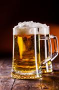 Beer on wooden table Stock Photos