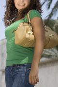 Hispanic teenaged girl carrying shoulder bag - stock photo