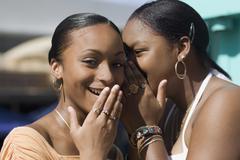 African teenaged girls telling secret - stock photo