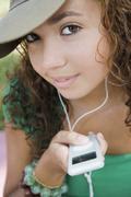 Hispanic teenaged girl holding mp3 player Stock Photos