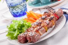 Stock Photo of meat skewers with carrots and salad