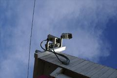 Security Cameras on Building Amidst Blue Sky - stock photo
