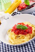 spaghetti with tomato sauce on classical home table - stock photo