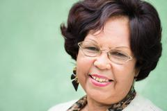 portrait of happy elderly black lady with eyeglasses smiling - stock photo