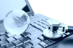 stethoscope and globe on a laptop keyboard - stock photo