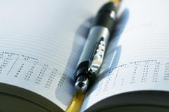 Pen lying on opened  notebook Stock Photos