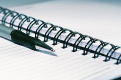 Silver-blue pen lying on opened  notebook Stock Photos
