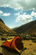 Stock Photo of yellow tent in the mountain