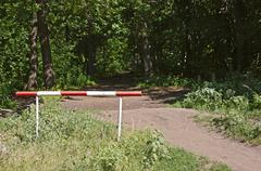 barrier on the road in the woods - stock photo