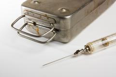 Old medical syringes and metal box Stock Photos