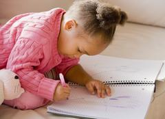 African girl drawing in notebook Stock Photos