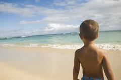 Stock Photo of Pacific Islander boy looking at ocean