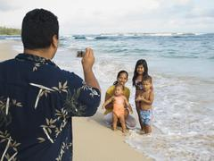 Pacific Islander father taking photograph of family - stock photo