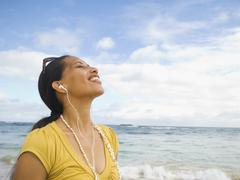 Stock Photo of Pacific Islander woman listening to mp3 player
