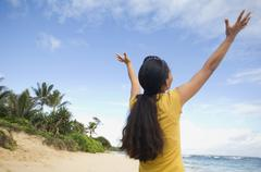 Pacific Islander woman with arms raised at beach - stock photo