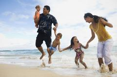 Pacific Islander family jumping in ocean surf Stock Photos