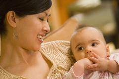 Asian mother smiling at baby - stock photo