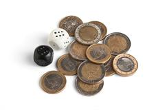 Pile of coins and dice Stock Photos