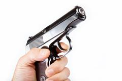 Gun in hand on a white background. Stock Photos