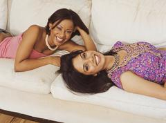 Multi-ethnic women laying on sofa Stock Photos