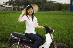 Asian woman sitting on motor scooter Stock Photos