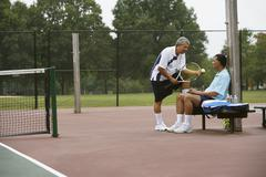 Multi-ethnic men talking on tennis court Stock Photos