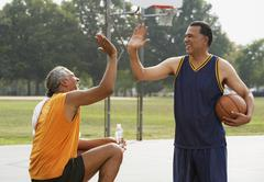 African men high-fiving on basketball court Stock Photos