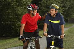 Multi-ethnic men riding bicycles - stock photo