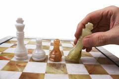 Hand poses a chess piece on the board Stock Photos