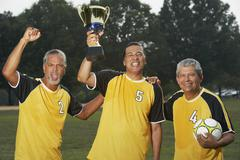 Multi-ethnic men holding soccer trophy Stock Photos