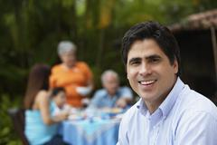 Hispanic man with family in background Stock Photos