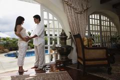 Pregnant Hispanic couple standing in doorway Stock Photos