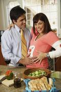 Pregnant Hispanic couple hugging - stock photo