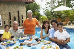 Multi-sukupolvien latinalaisamerikkalainen perhe syö ulkona Kuvituskuvat