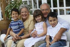 Hispanic grandparents hugging grandchildren Stock Photos