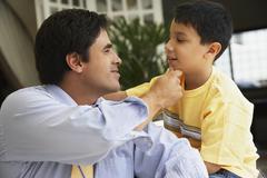 Stock Photo of Hispanic father touching son's chin
