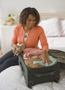 African woman packing suitcase Stock Photos