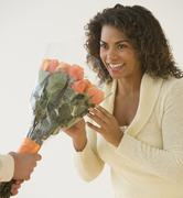African woman receiving bouquet of flowers Stock Photos