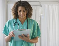 African female doctor looking at chart Stock Photos