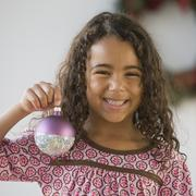 African girl holding Christmas ornament Stock Photos